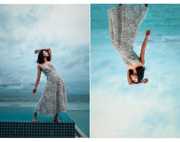 Foto de uma mulher na borda de uma piscina usando um vestido branco rendado com o mar no fundo, sendo editada pelo AirBrush