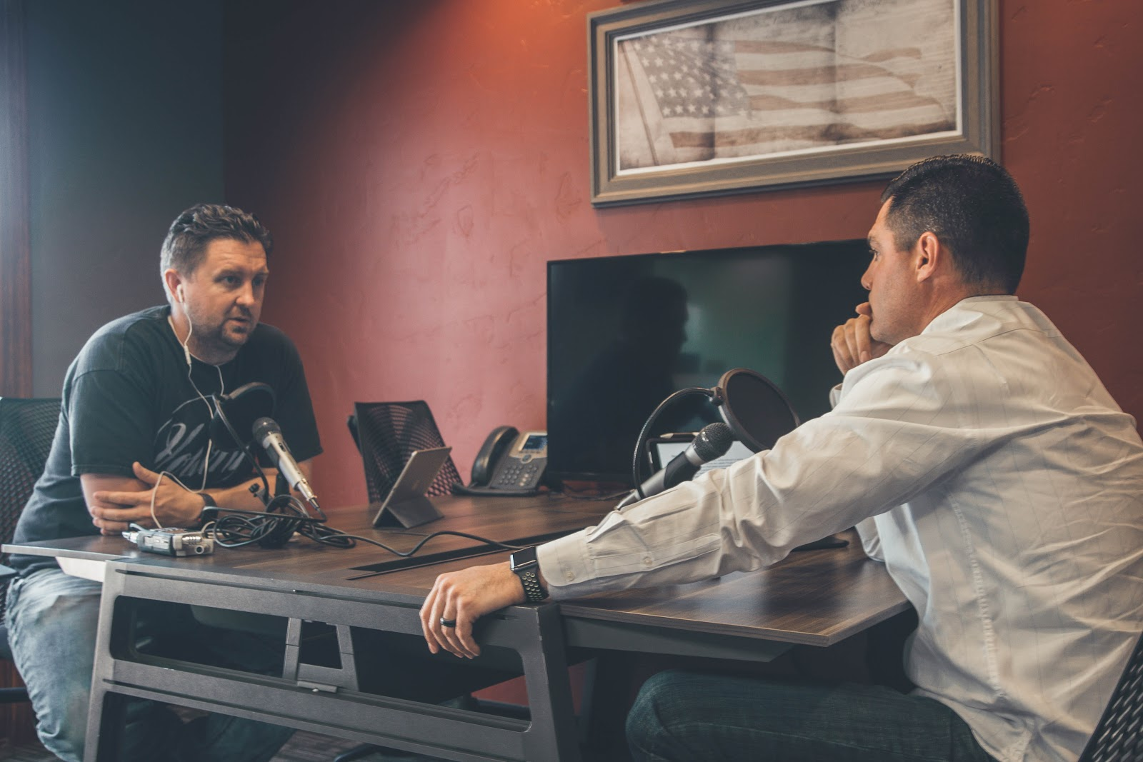Two men discussing how to spread the gospel while recording a podcast.