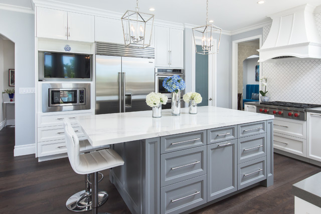u-shaped grey and white kitchen with grey and white shaker cabinets, white countertops, white range hood and chrome bar pulls