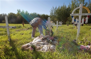 A woman we can only identify as Ness, tends to the grave of her daughter, Jade, who died of pneumonia while in foster care in 2009. This photo has been altered to remove Jade's real name from the cross at her grave. A subsequent fatality inquiry identified numerous deficiencies in the girl's care and repeated breaches of provincial rules.