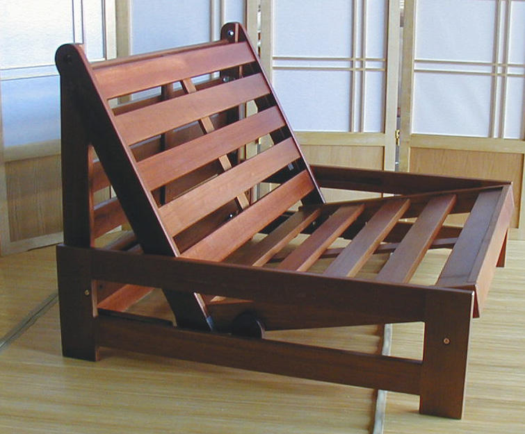 A futon mattress frame has armrests and is designed to bend into an L shape for the chair shape.