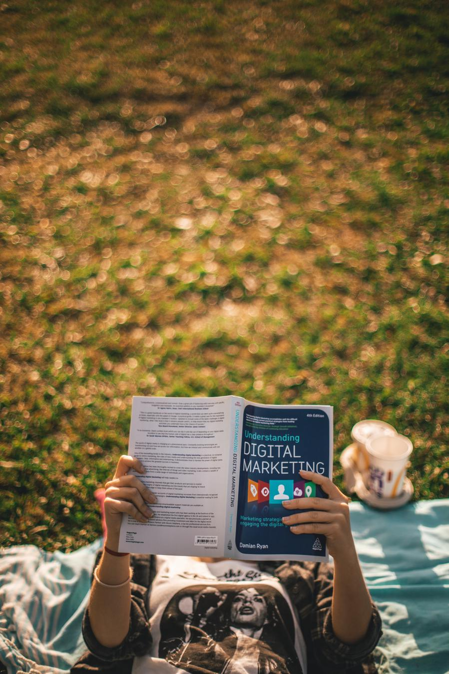 Person studying a book on digital marketing outside