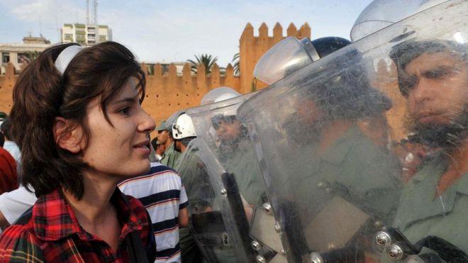 Мирные протесты с большей долей вероятности привлекают на свою сторону население. На снимке - участница демонстрации в поддержку реформ перед бойцами сил безопасности в Марокко (2011 г.)