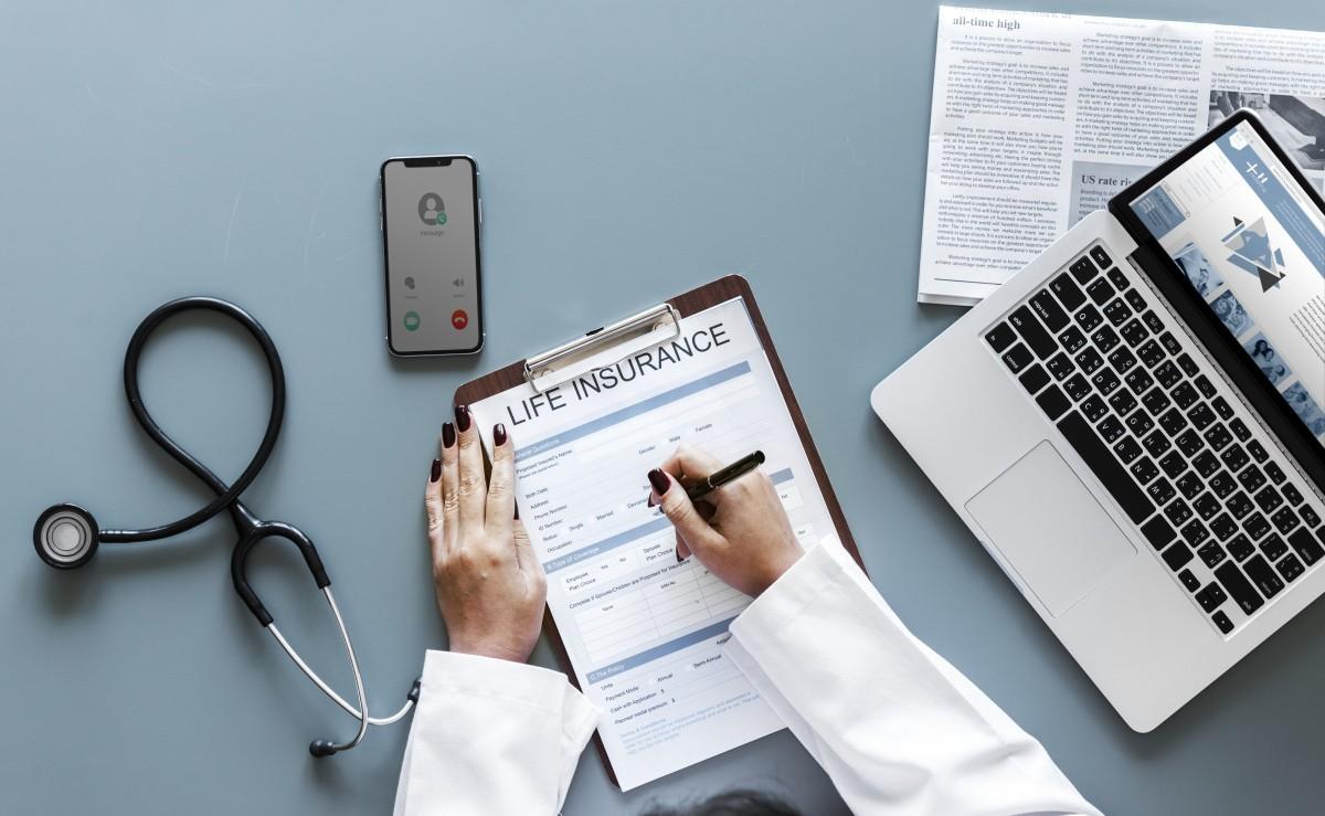 Planos de saúde para MEI em 2021: imagem de uma médica assinando contrato de plano de saúde com instrumentos médicos sobres a mesa.