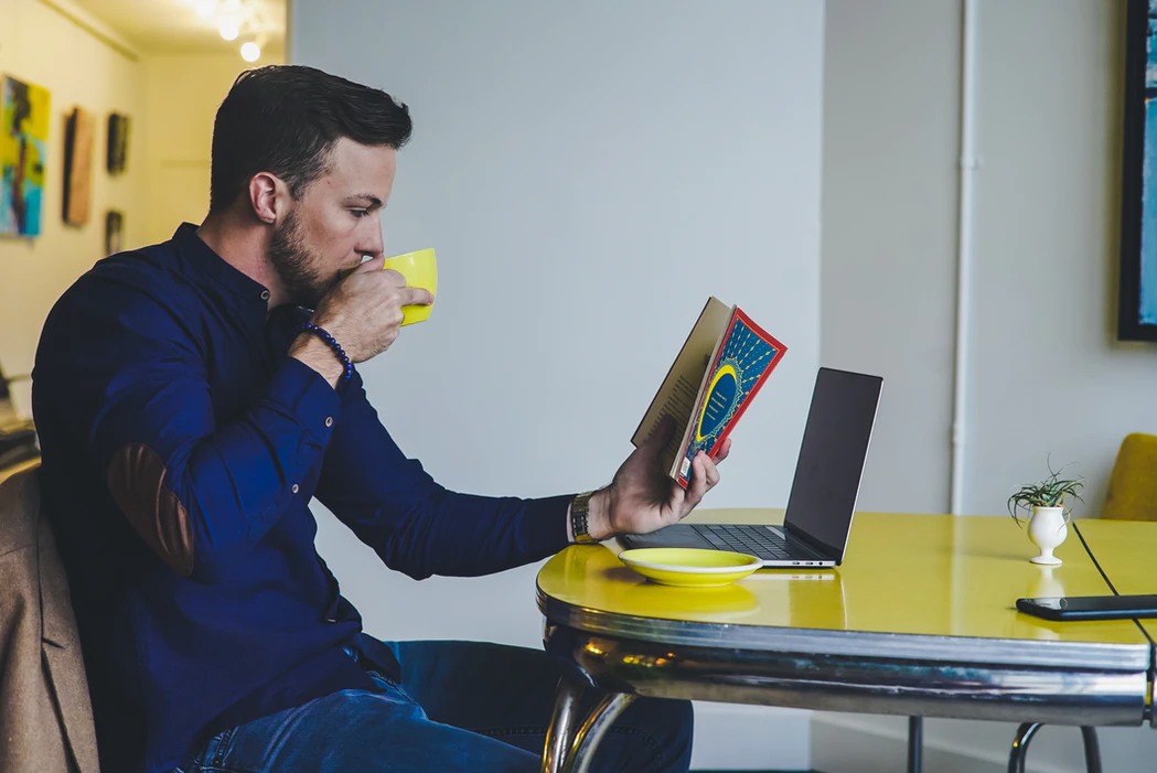 man drinking coffee while reading a book