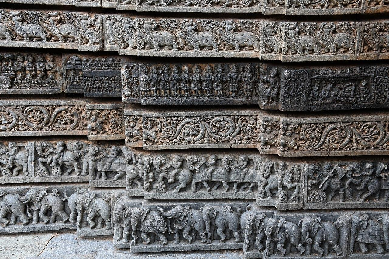 The carved horizontal layers of the mantapa. Notice the elephants at the base followed by fighting warriors, horses, decorative foliage, dancers etc.