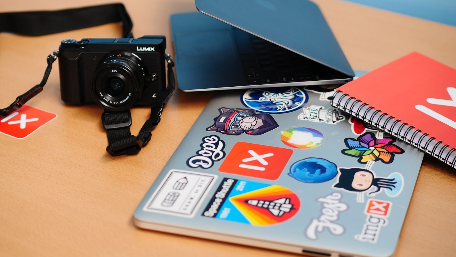 Custom stickers on a laptop, table. Camera, laptop, and notebook laying on table