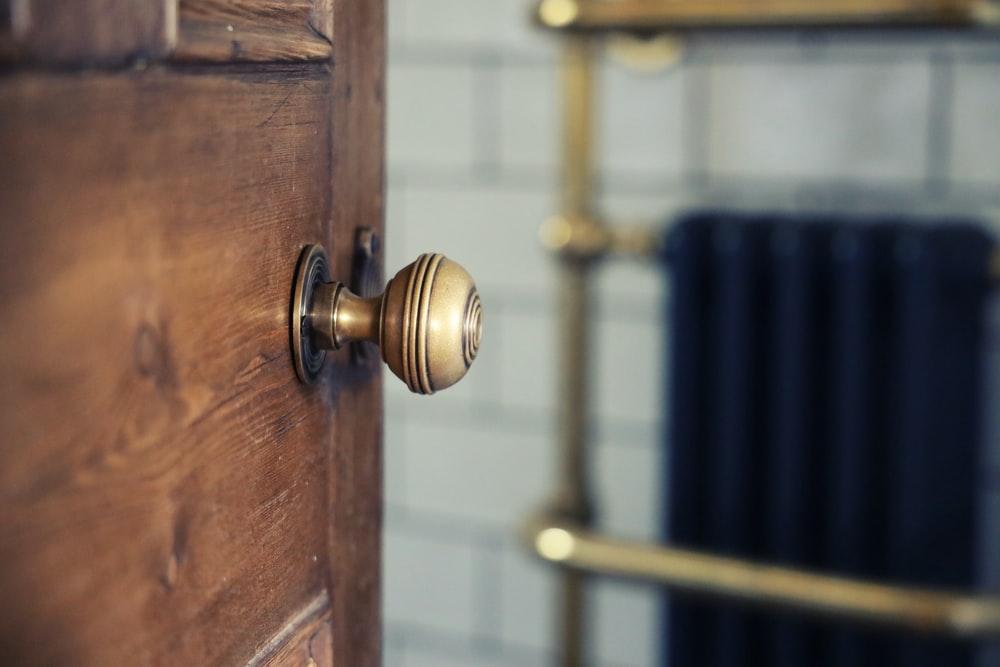 brass door knob on brown wooden door