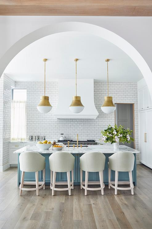 large contemporary white kitchen with gold pendant lights and blue island