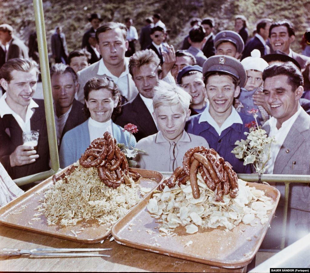 Приехавшие на фестиваль в западной Венгрии в 1959 году любуются горами колбасы