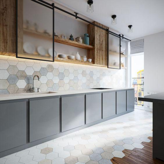 Cozinha com revestimento hexagonal multicolor na parede da pia e na metade do piso, outra metade de madeira, armário superior amadeirado e inferior cinza.