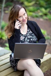A person sitting on a bench with a computer  Description automatically generated with low confidence