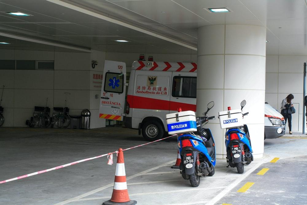 blue and white motorcycle parked beside white and red fire extinguisher