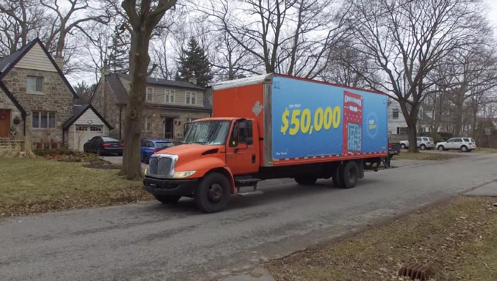 OLG truck-side ad with a crossword ticket on the truck and big yellow font saying $50,000.