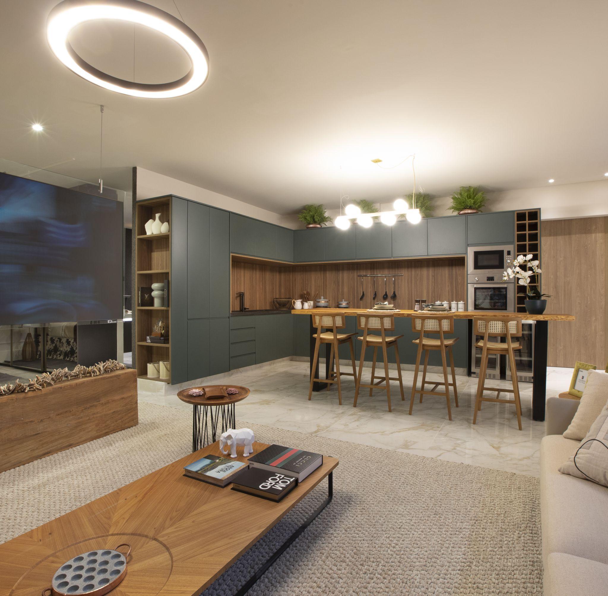 Cozinha integrada a sala de estar com armário cinza escuro com detalhes amadeirado, bancada de madeira com quatro cadeiras, porcelanato em tom neutro, tapete nude