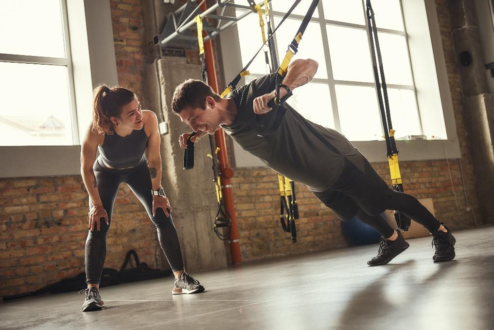 sports equipment and healthy foods pictured against wooden background, personal trainer working with client, fit woman doing a lunge, personal trainer guiding a client in a barbell curl, personal trainer monitoring client's form during an exercise, personal trainer showing client how to lift weights correctly