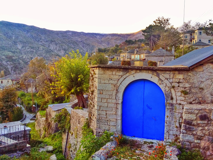 Many of the homes have blue doors in the mountainside village of Kalarrytes in Greece.