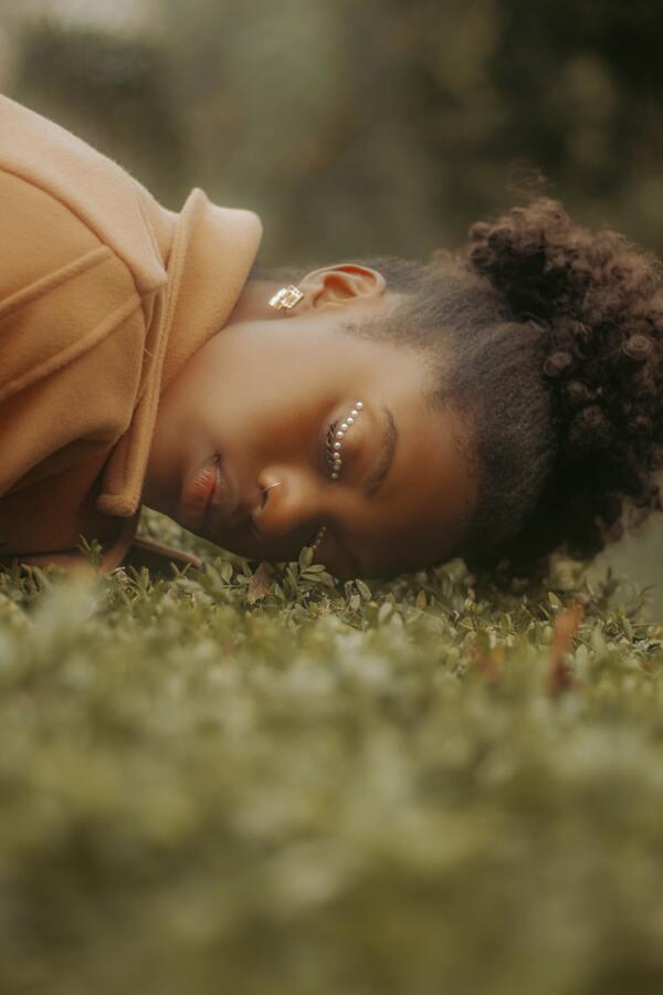 foto de uma mulher negra deitada na grama com pérolas coladas no olho
