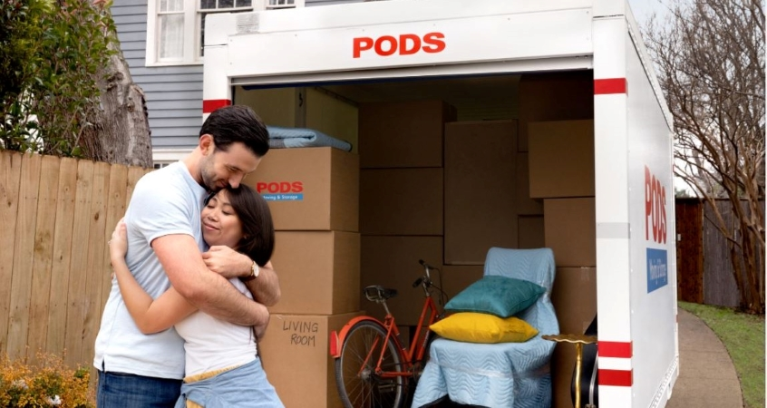 A couple hugging in front of their PODS portable moving container.