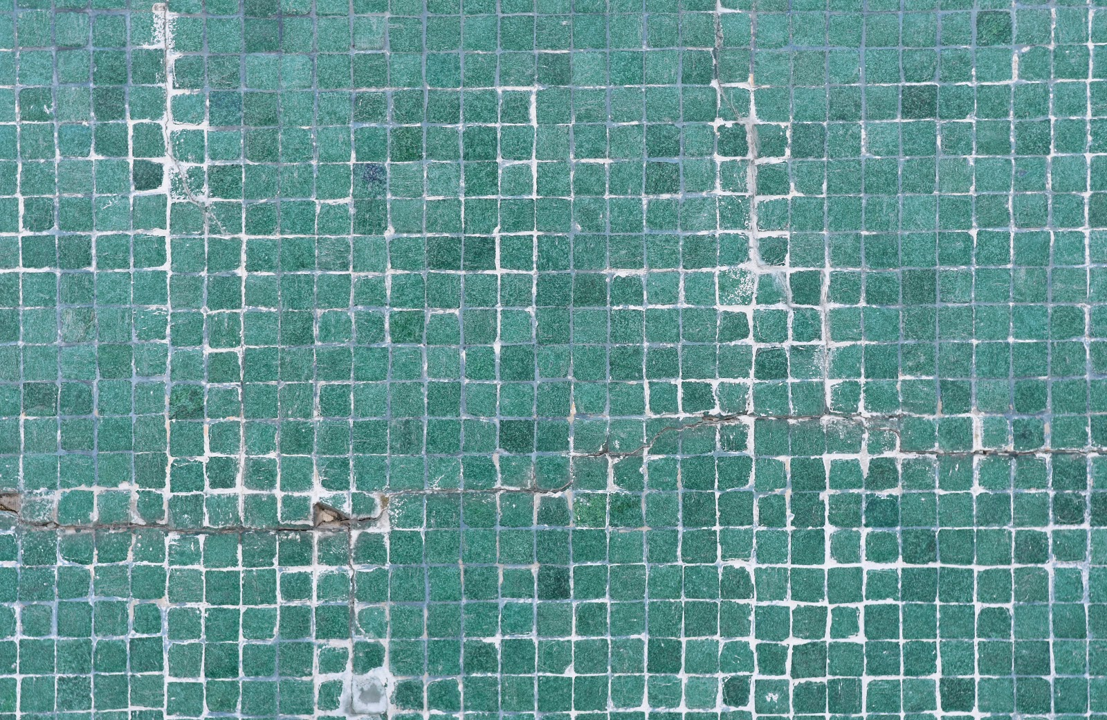 cracked tiles on a concrete swimming pool wall