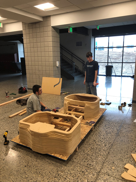 Students working on building the mold by stacking parts cut from MDF.