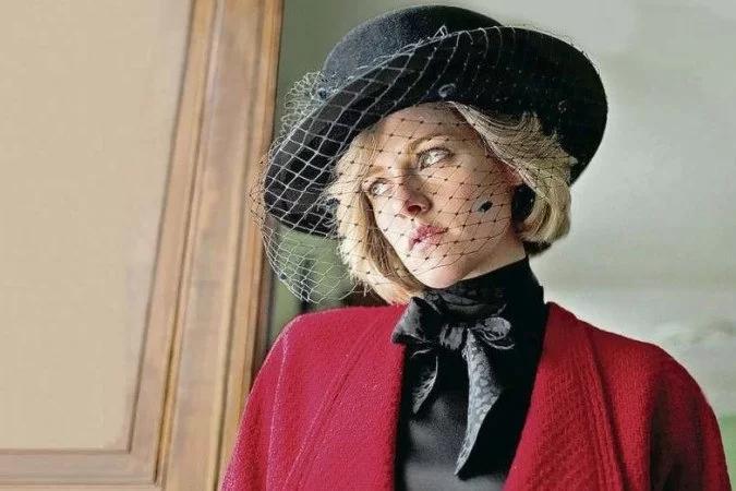Mulher branca loira de cabelos curtos veste chapéu preto com tela sob o rosto, blusa preta com laço e casaco vermelho. Filme Spencer. Foto: Reprodução.