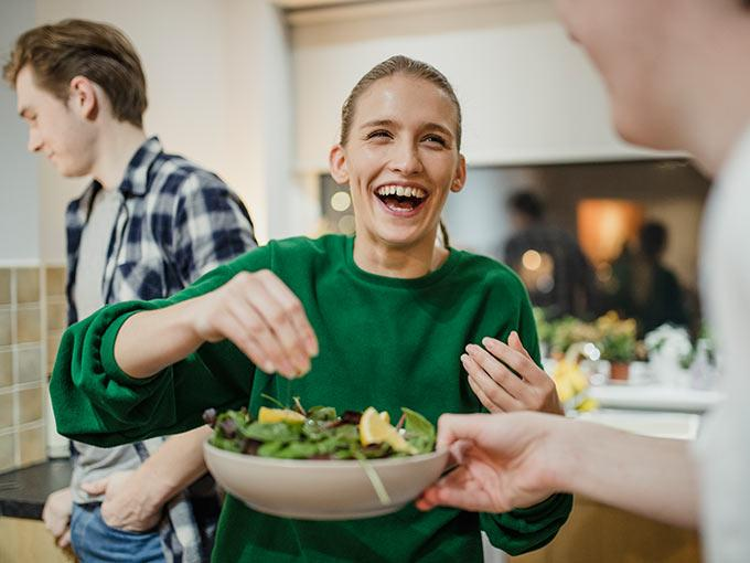 Junge Menschen bereiten in der Küche einen Salat zu - frische Lebensmittel mit einer niedrigen Energiedichte erleichtern das Abnehmen bei Diabetes.