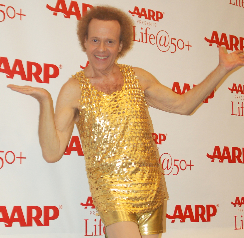 Richard Simmons posing in gold tanktop and shorts