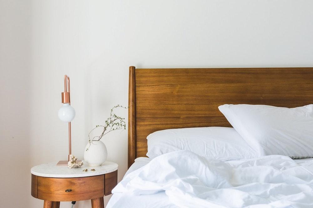 A bed with a white duvet and a bedside table with a plant