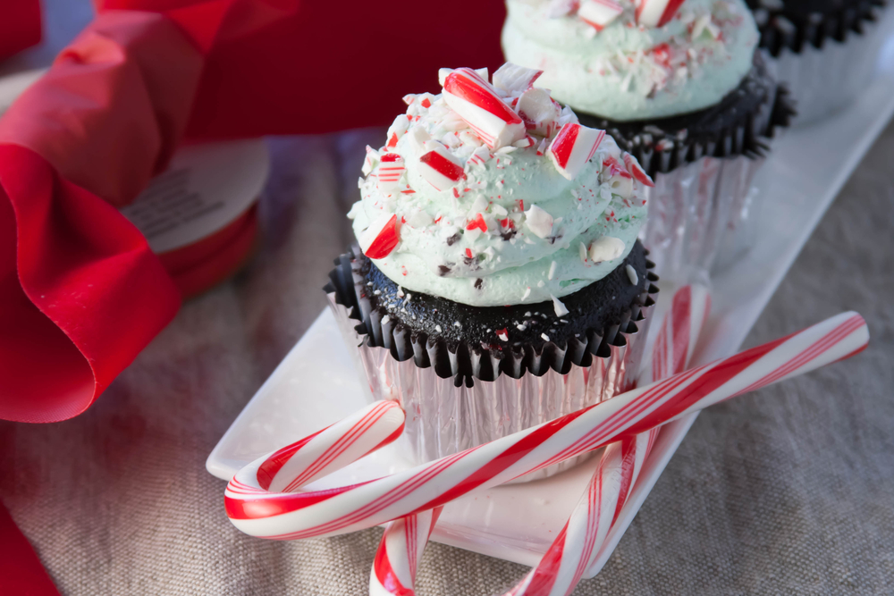 cupcake topped with crushed candy canes with a couple of candy canes on the tray
