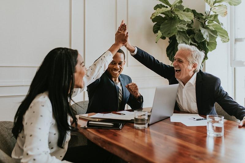 Várias pessoas comemorando em um escritório de trabalho e dando as mãos.