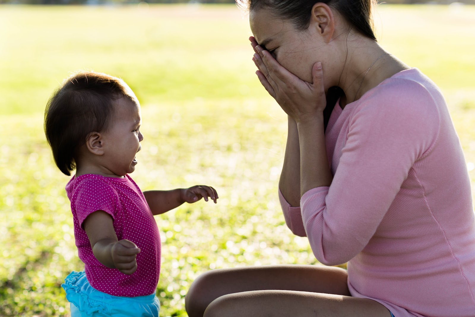 A crying baby looking at her mother in a field, covering her face crying