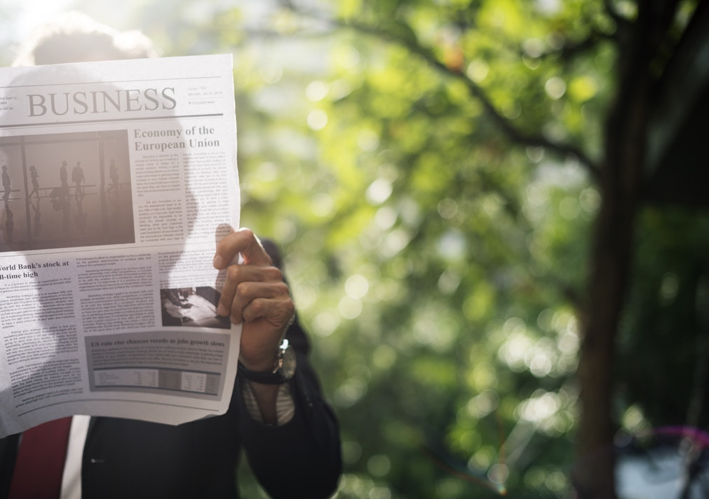 someone reading a business newspaper business health meter