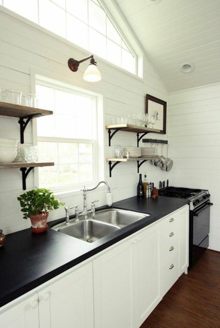 black and white farmhouse kitchen with white shiplap walls, wood open shelves, matte black countertop and white vintage shaker cabinets