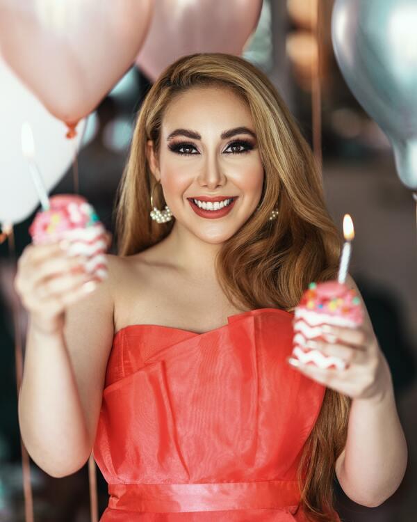foto de uma mulher segurando dois cupcakes com vela