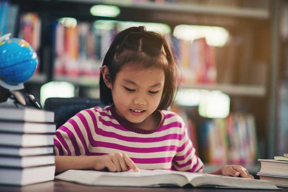 Criança sentada em cima de mesaDescrição gerada automaticamente com confiança média