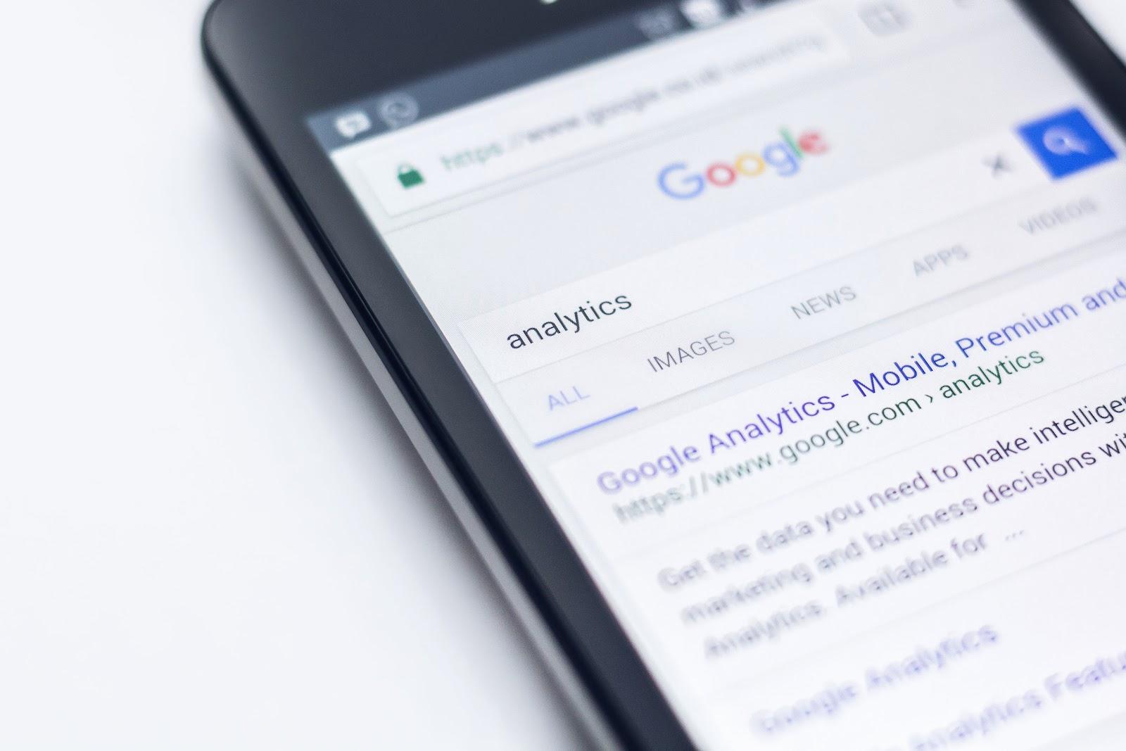 """Celular em cima de uma mesa branca. Na tela do dispositivo, os resultados de uma pesquisa da palavra """"Analytics"""" feita no Google."""