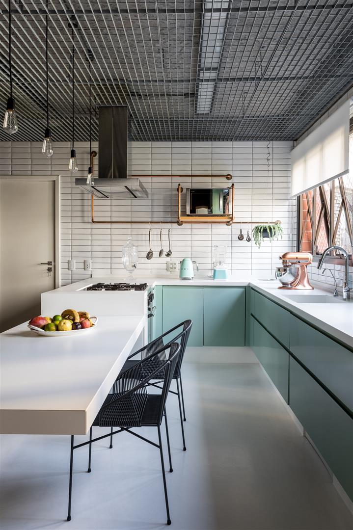 Cozinha em estilo industrial com azulejos do metrô e piso porcelanato na cor branca, luminárias pendentes, armários verde claro e branco, com bancada branca de cadeiras pretas.