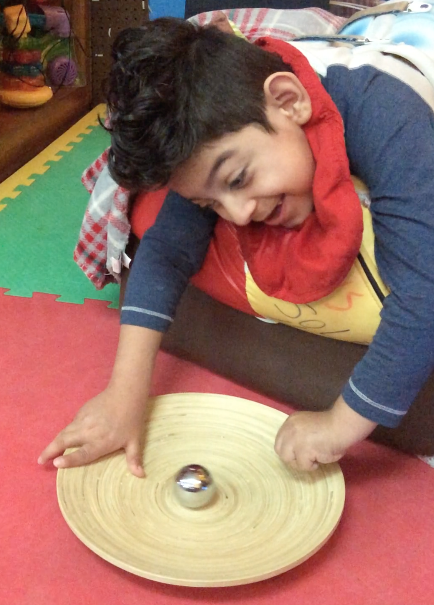 Student smiles as he plays with a metal ball on a tray.