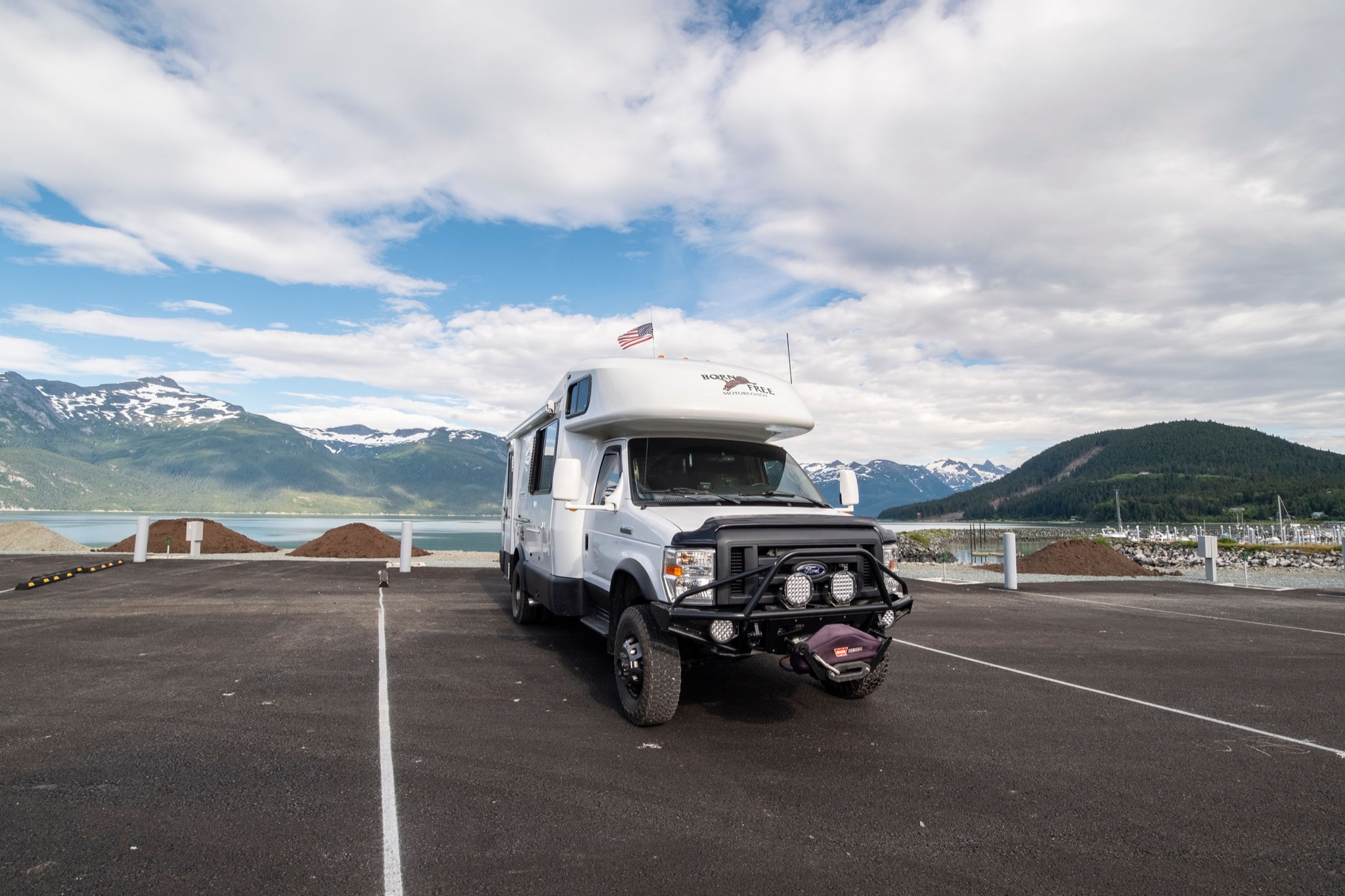 RV van parked in parking lot in front of mountains and lake.