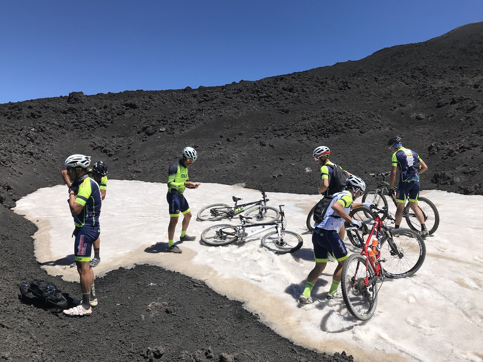 Cyclists in snow with bikes at top of Mount Etna, Sicily, Italy