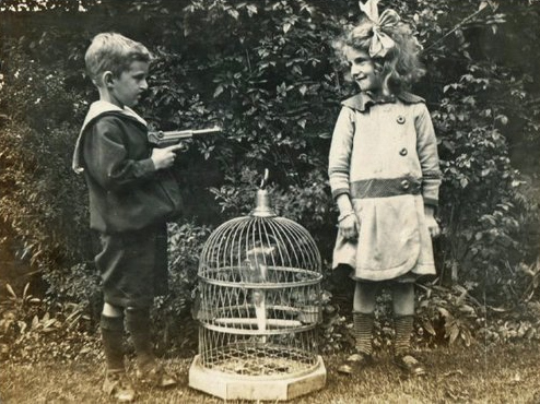 Antique photo, unknown providence, era 1890s, two children and a birdcage, boy on left holding toy gun pointed at laughing girl on right.