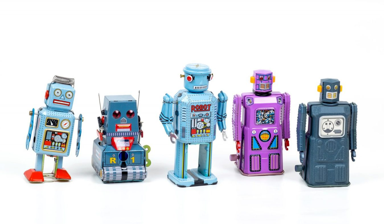 Little toy robots in a row against a white background