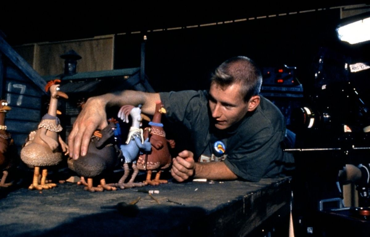 Behind the scenes of Chicken Run: an animator wearing a black t-shirt in the Aardman studios moves some of the stop motion chicken models on a table, they are about the size of his hand.