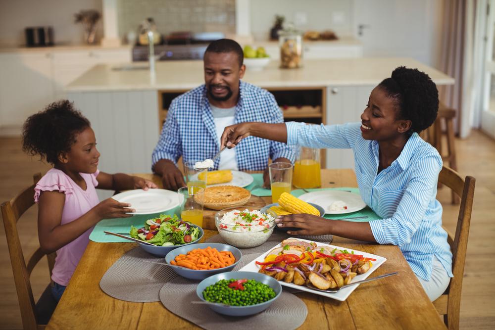 família sentada na mesa comendo