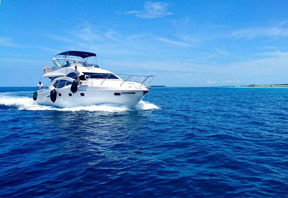 white and blue yacht on sea under blue sky during daytime