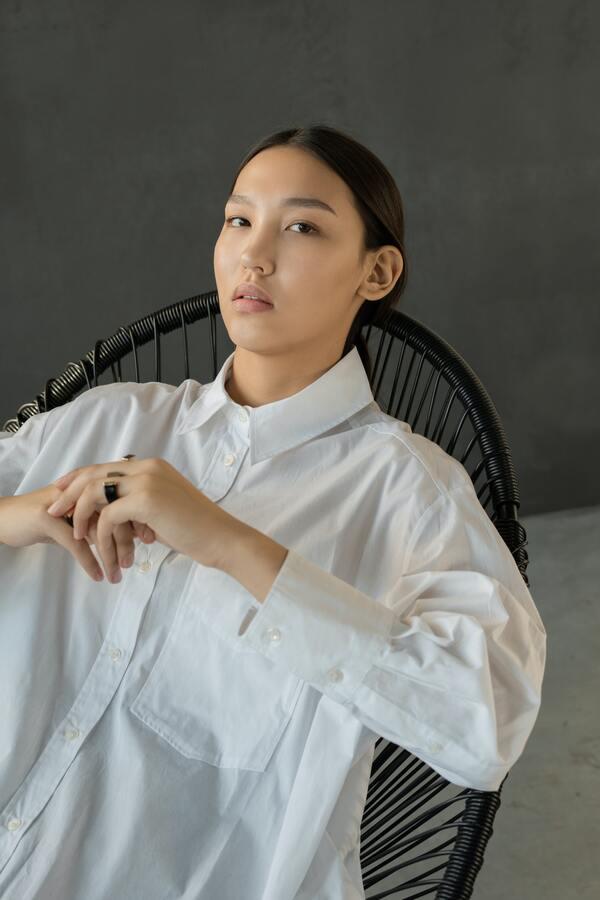 Mulher asiática usando uma camisa branca, sentada.