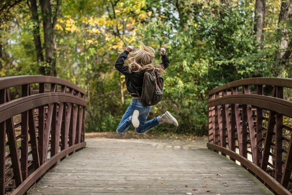 School girl jumping happily on bridge