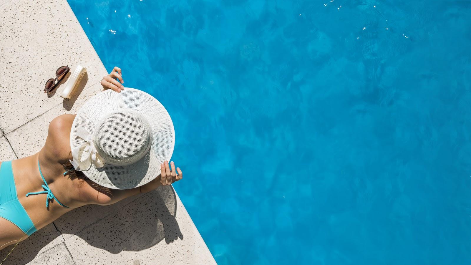 Mulher de chapéu tomando sol na piscina