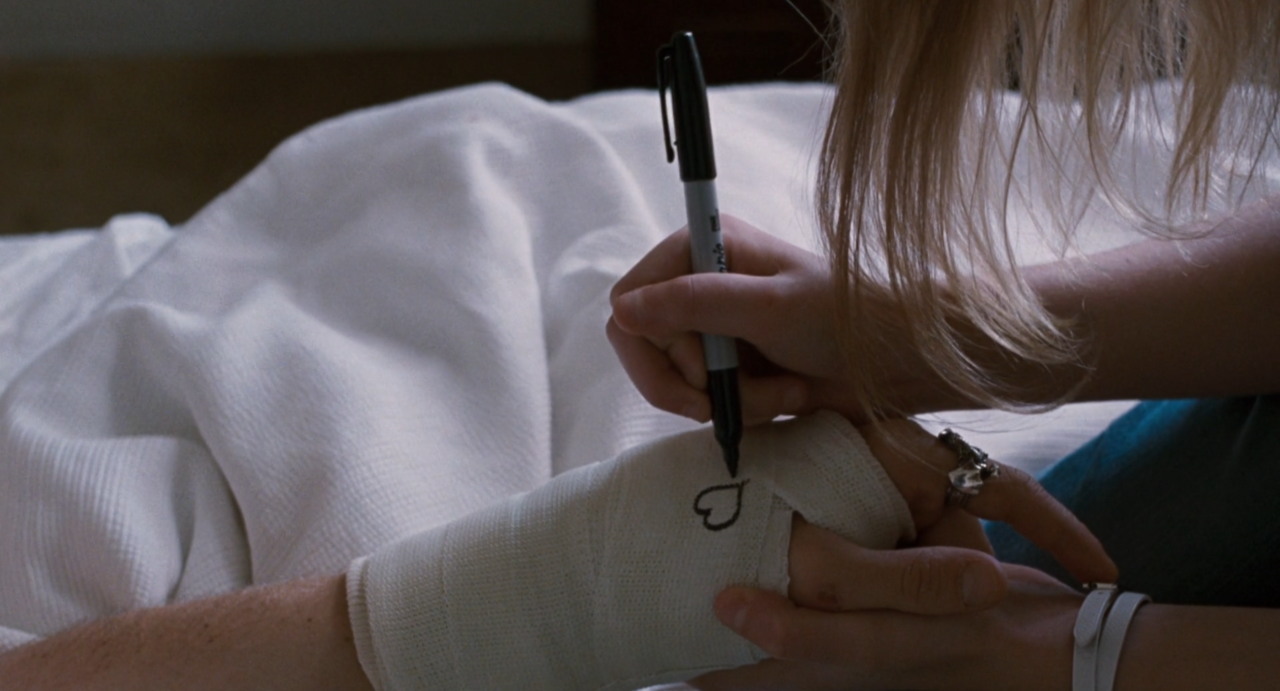 A close still of Cleo signing Johnny's cast with her name and a heart by using a back marker when his cast is still new and unsigned. They are in bed, crisp white sheets are seen in the background, and Cleo is holding his hand while she does it for stability. Johnny is wearing a visible silver ring on his index finger.